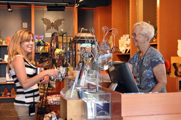 Customer and cashier smiling at gift shop counter