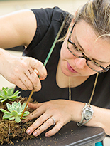 Class participant creating wreath from succulents