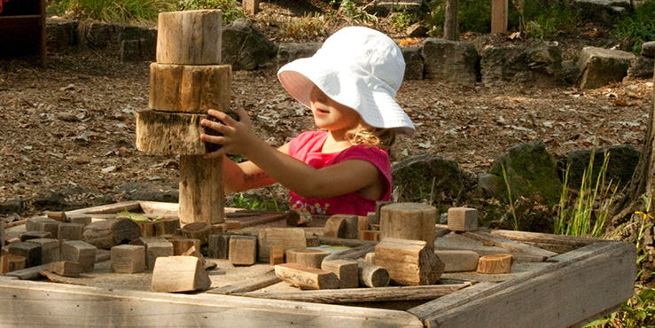 Girl stacking tree blocks