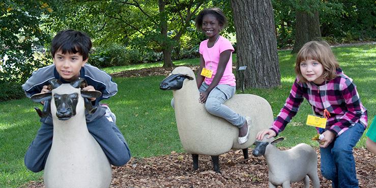 Kids posing on sheep sculptures