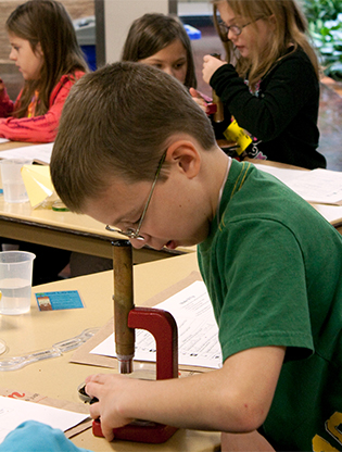 Boy looking at soil through a microscope
