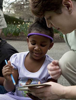Girl journaling with instructor