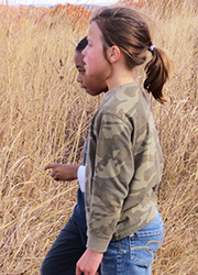 Girl walking through autumn prairie