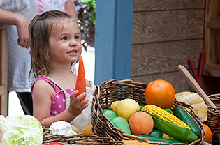 Girl playing with toy vegetables in Children's Garden