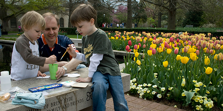 Dad and sons paint spring flowers during a Great Green Adventures program