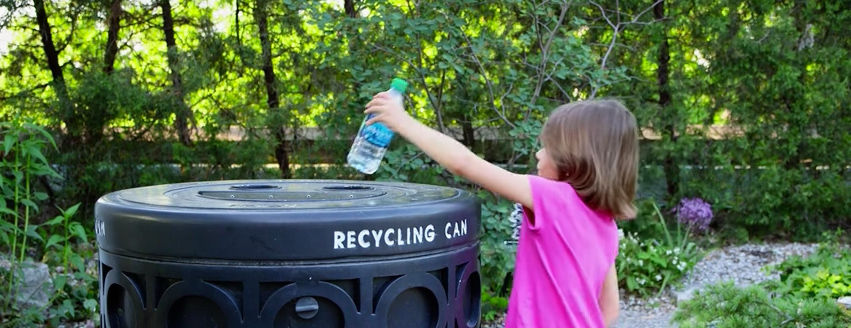 Young girl recycling a water bottle