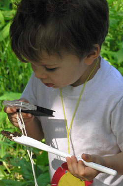 Boy looking at soil through hand lens