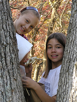 Two Habitat Helpers examining a tree