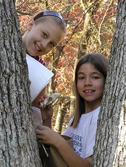 Two Habitat Helpers examining a tree