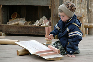 Boy builds and balances using pieces of wood