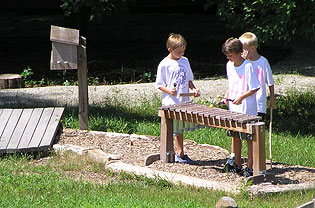 Boys make music on a wooden marimba