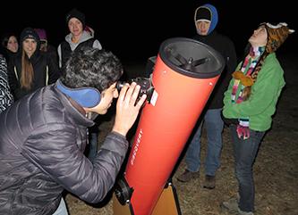 Student looking through telescope