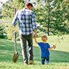 Man and boy walking with tree seedling and shovel