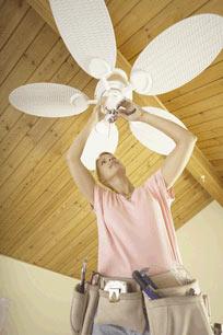 Homeowner installing a ceiling fan
