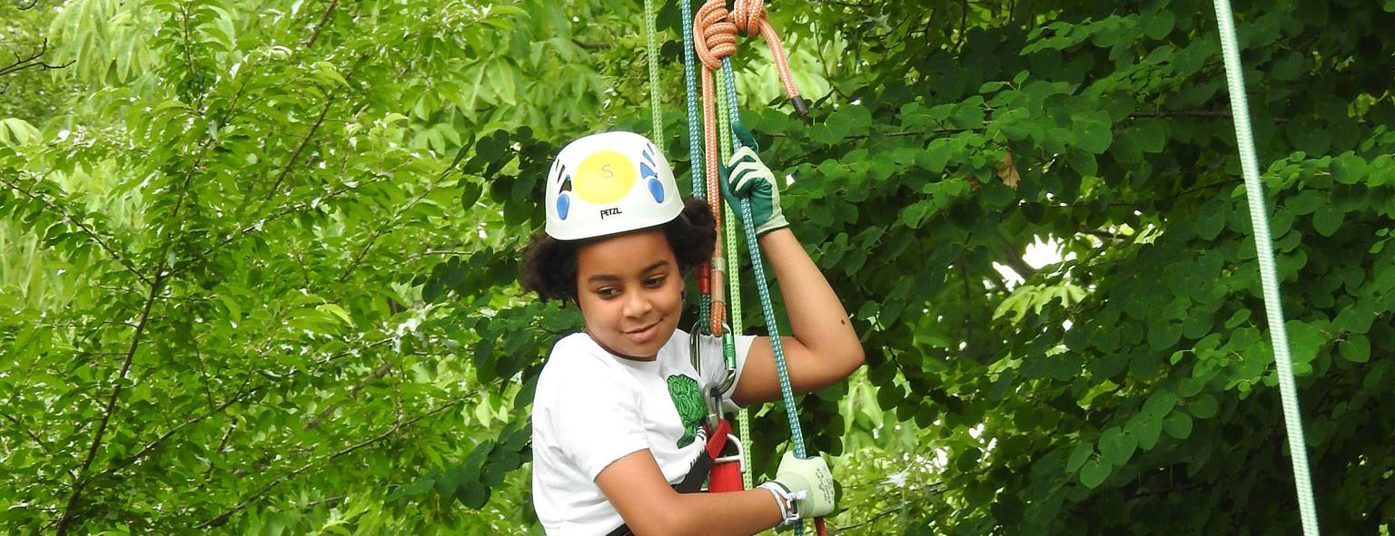 Girl hanging in tree during Canopy Climb experience