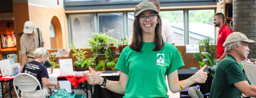 Young woman in green t-shirt welcomes visitors to the Green Living Festival