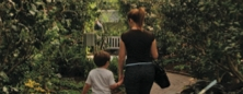 Woman and child walking through conservatory