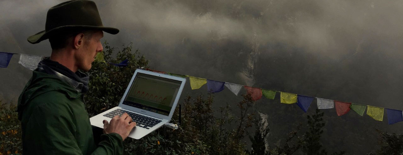 man works on laptop overlooking the Himalayas