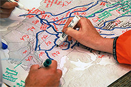 Hands drawing watersheds on map
