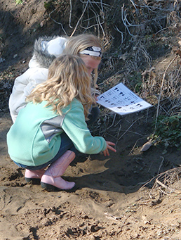 Fourth-graders study animal tracks in mud on field trip lead by ECO-ACTors