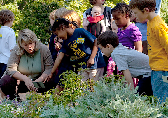 Instructor with young students crouched around plants