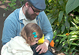 Father and daughter in butterfly conservatory