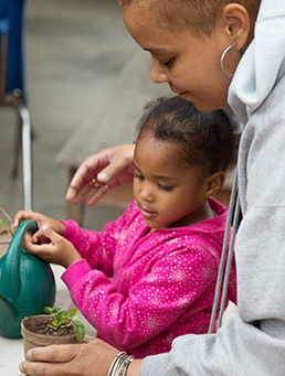 Mother and daughter potting a plant
