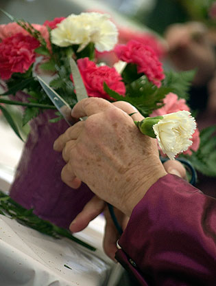 Closeup on hands arranging flowers